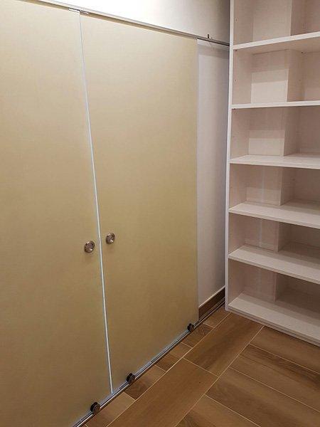 porta di color beige con pomelli argentati e accanto uno scaffale libreria di color bianco