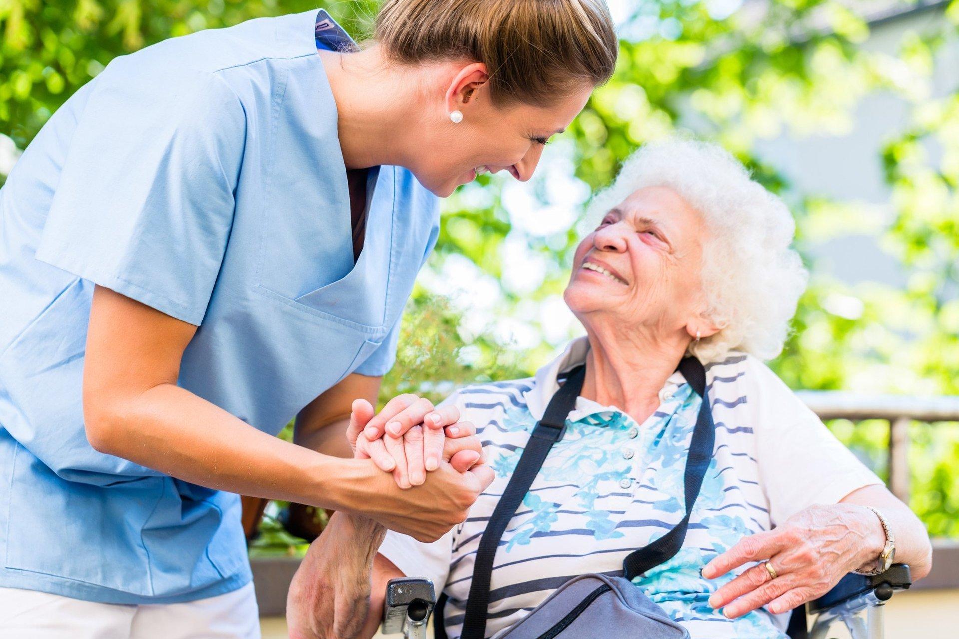 Sorridente badante che abbraccia felice donna anziana in casa di cura
