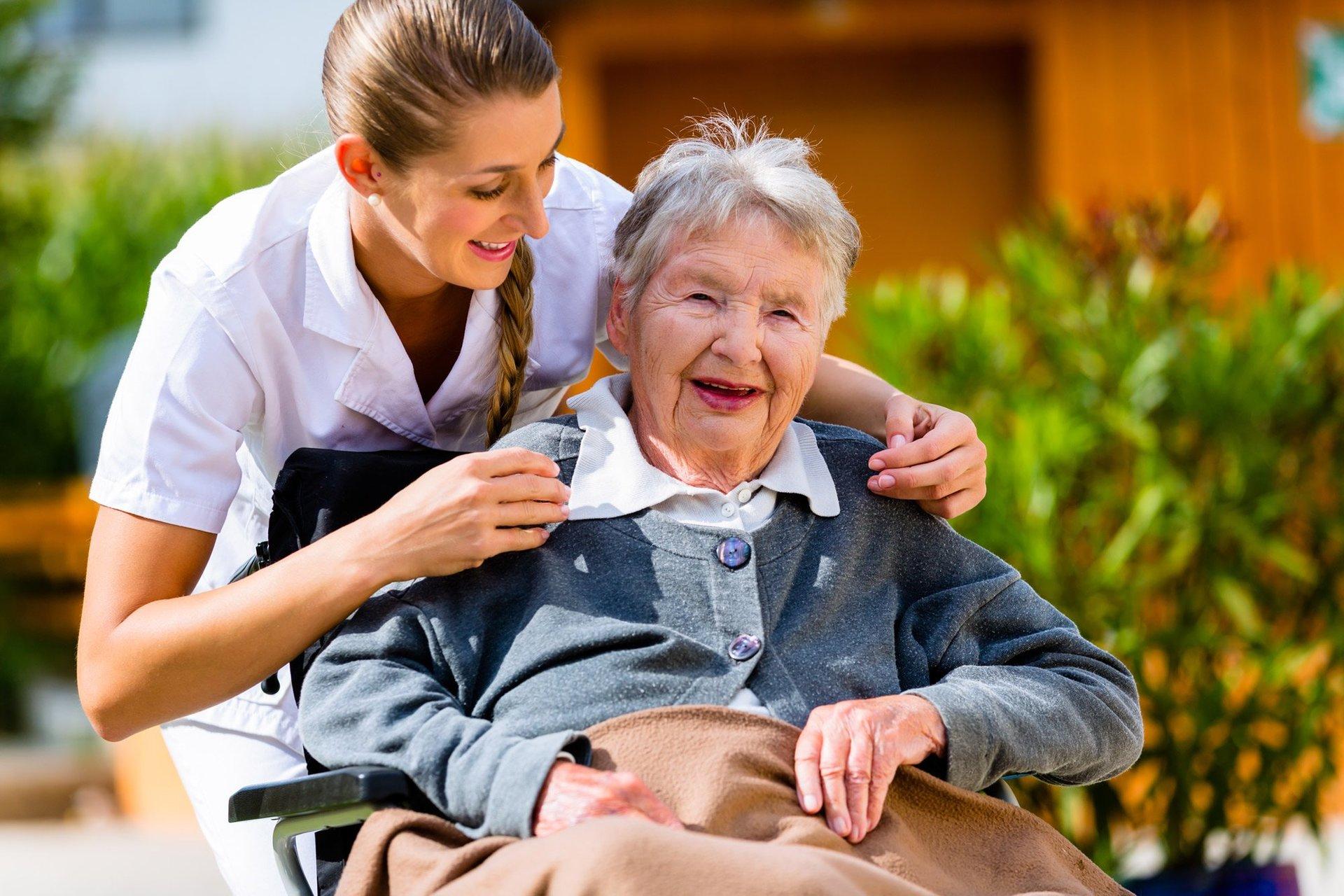Sorridente infermiera che abbraccia felice donna anziana in casa di cura