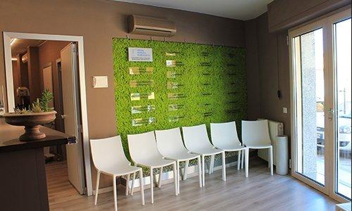 delle sedie bianche e dietro  un pannello verde a muro