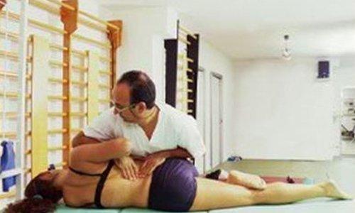 il dottore che applica pressione sulla schiena di una paziente a seguto della terapia manuale