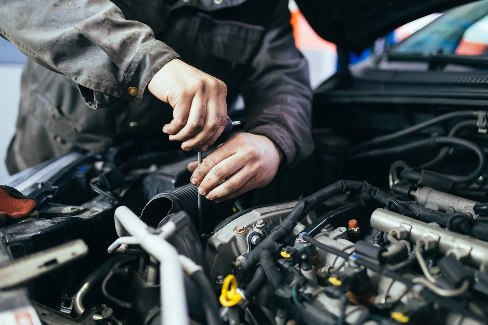 Mani di un tecnico dell'Autofficina al lavoro su un motore