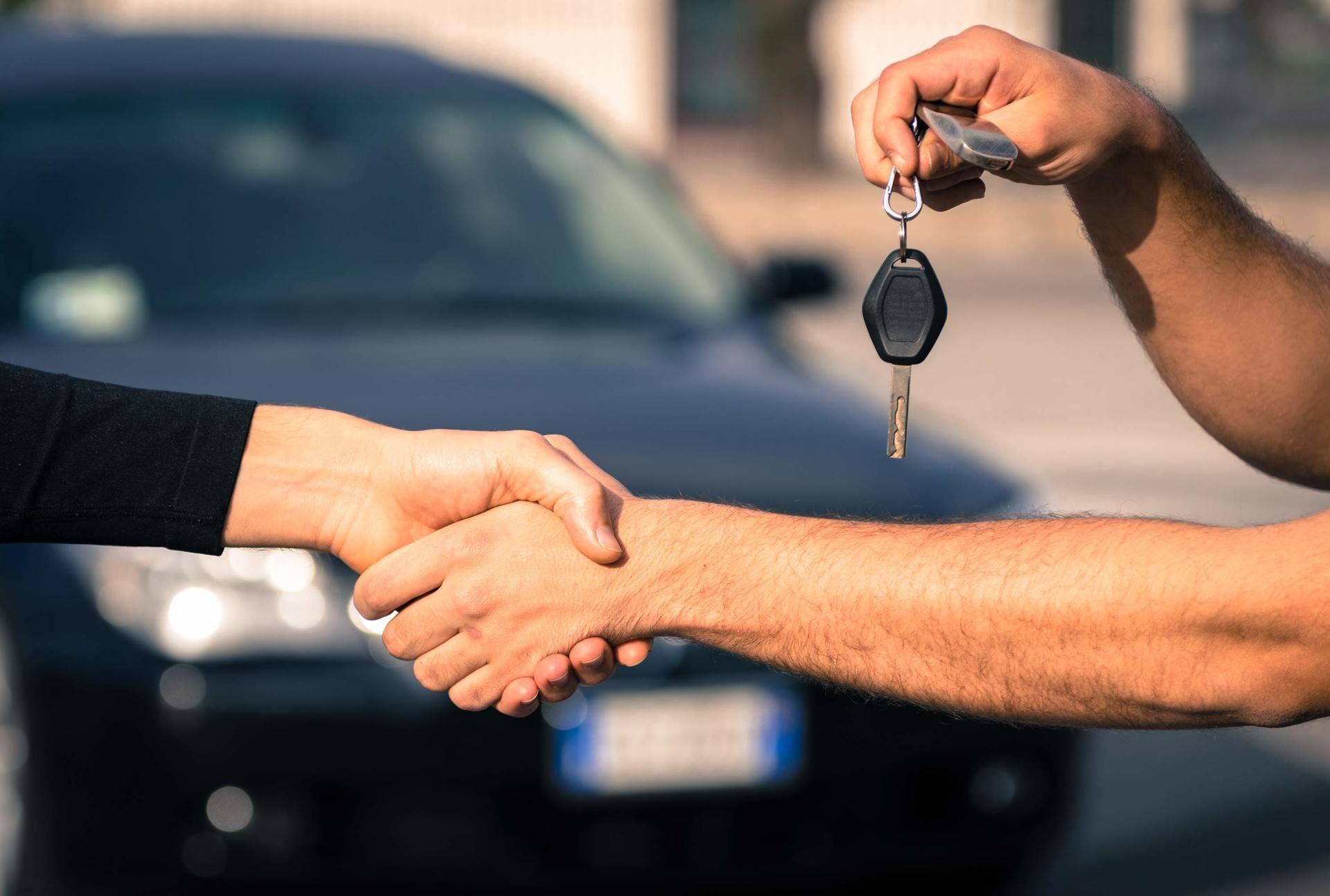 stretta di mano e consegna della chiave di un'auto