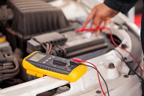 meccanico mentre ricarica la batteria di un auto