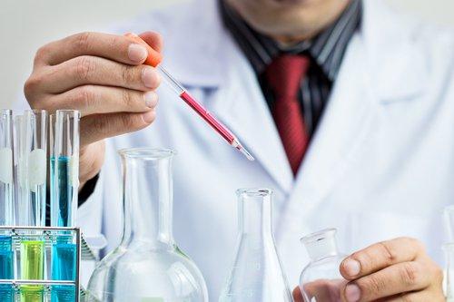 mano di un medico in possesso di una bottiglia di campione di sangue