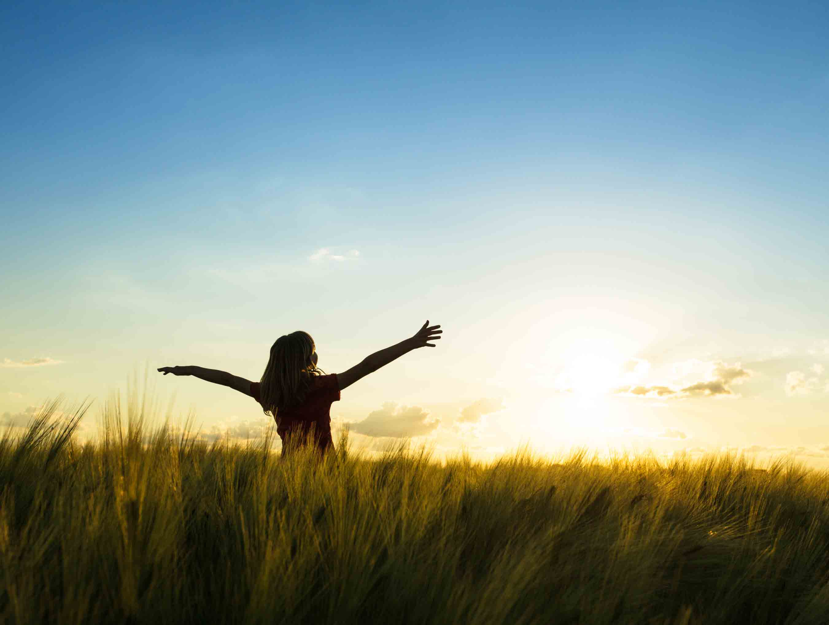 girl with arms wide open in field