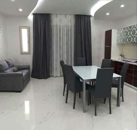vista interna di una sala da pranzo con divano e tende