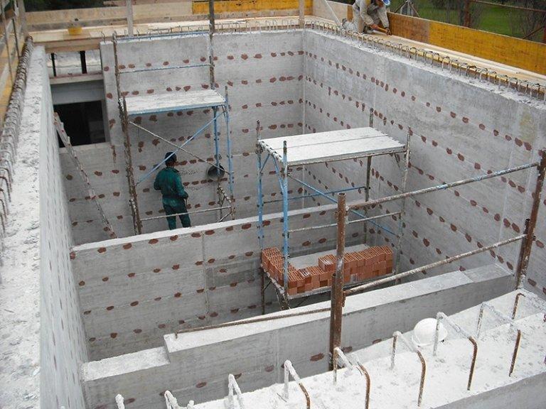 Operaio su impalcatura mentre costruisce fondamenta