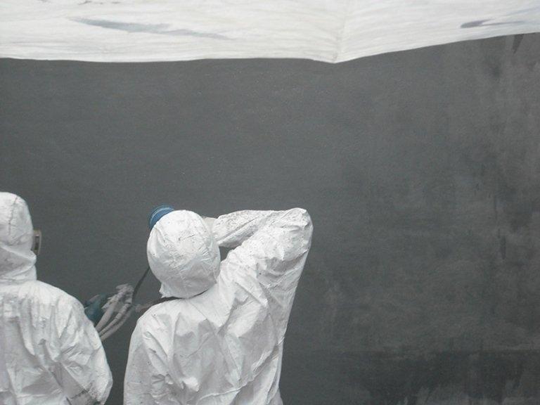 Operaio impermeabilizza parete in cemento
