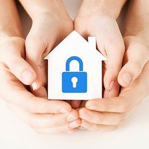 delle mani con una casa in miniatura con un lucchetto disegnato