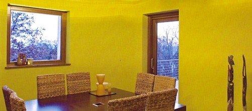 stanza con parete gialla e sedie in sughero