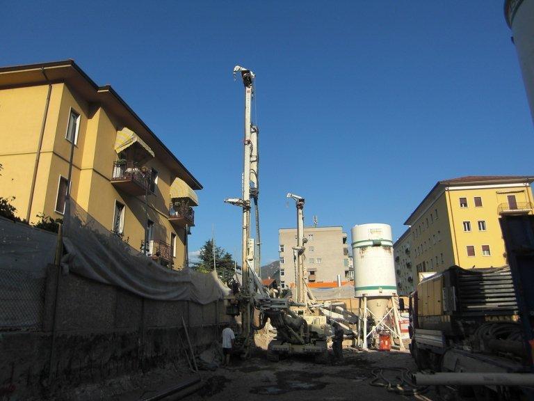 Dei macchinari con delle perforatrici in un cantiere vicino a dei condominii