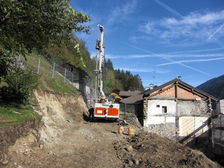 un macchinario con una perforatrice è accanto una casa in costruzione
