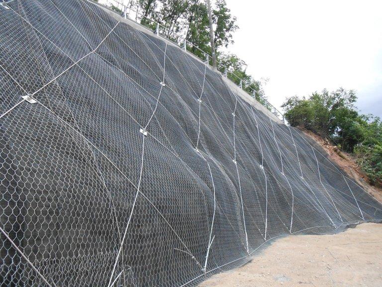 un muro in roccia coperto da una rete metallica