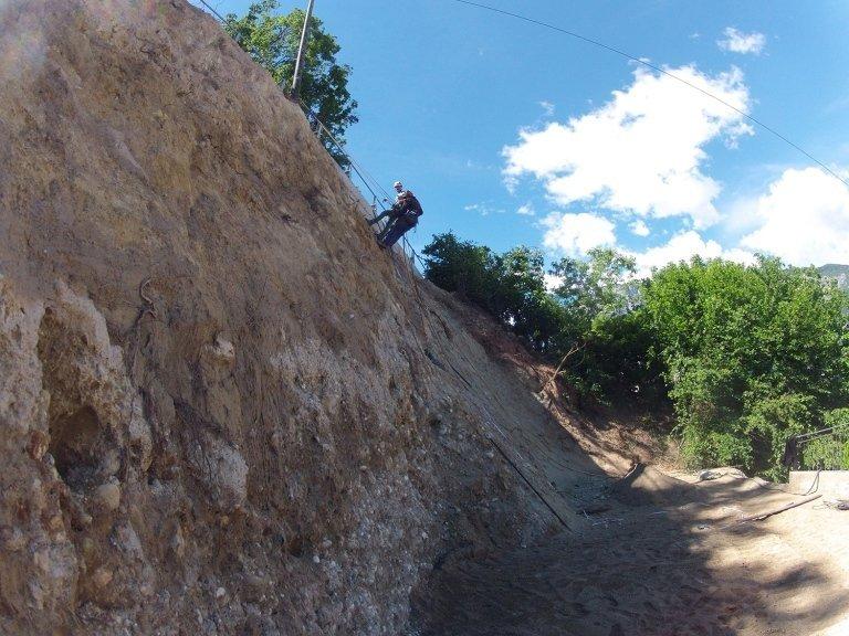 Un uomo con un'imbracatura che scende da una parete rocciosa