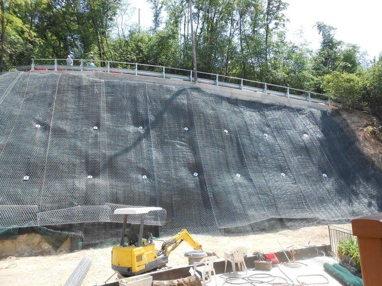 un muro in roccia coperto da una rete di metallo