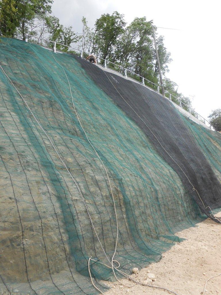 Un uomo mentre copre una parete rocciosa con una rete verde