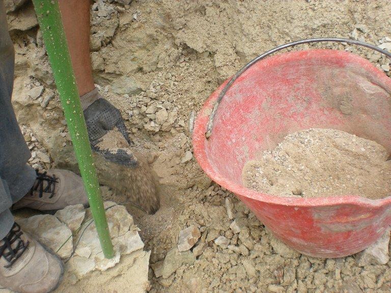 Un paletto verde conficcato nel terreno e un secchio con della terra