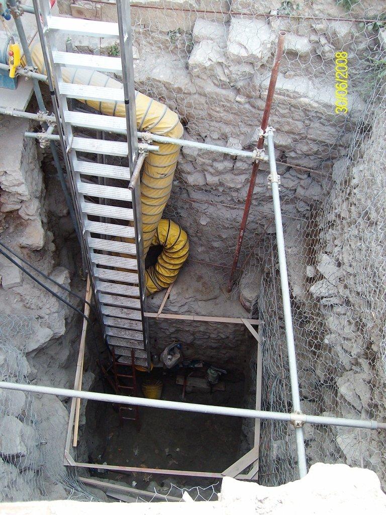 una scala in metallo nel buco di uno scavo roccioso