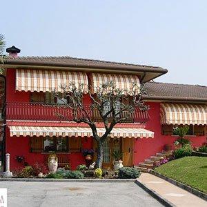 delle tende da esterno bianche a righe arancioni in una villa di color rosso con davanti un aiuola con delle piante e un albero