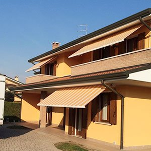 tende da esterno gialle a righe arancioni in una villa color sabbia