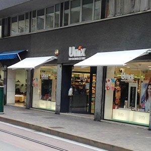 tende bianche da esterno in uno stabile grigio che ospita delle vetrine di un negozio