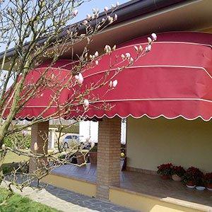 delle tende rosse spioventi a righe bianche vicino a un porticato con delle colonne di mattoni arancioni e lo stabile di color giallo