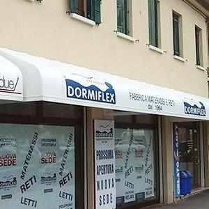 una tenda bianca ion scritto Dormiflex all'esterno di un negozio con 3 vetrine