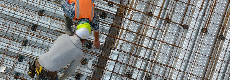 operai fissano dei tubi in ferro su un tetto