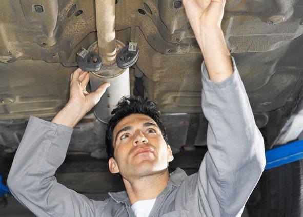 mechanic working on exhaust