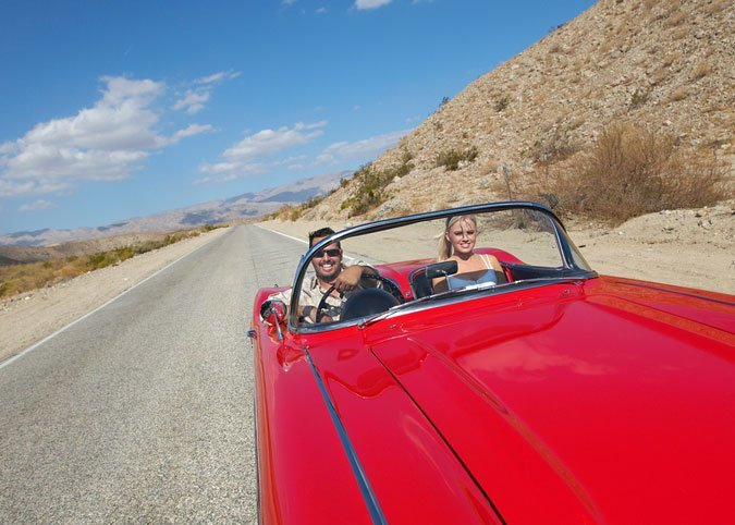 couple driving in a classic car