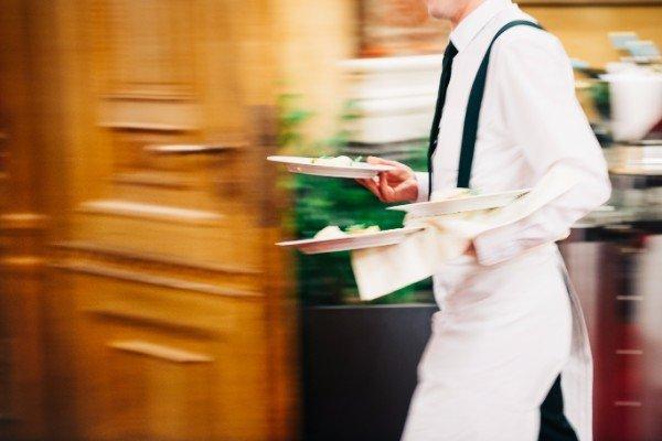cameriere che porta dei piatti