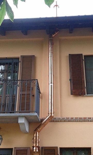 una grondaia in una facciata  con delle persiane in legno