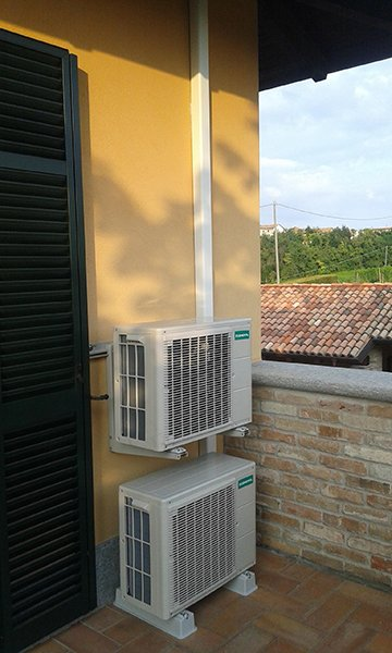 due motori di alcuni condizionatori e una grondaia all'esterno di una casa