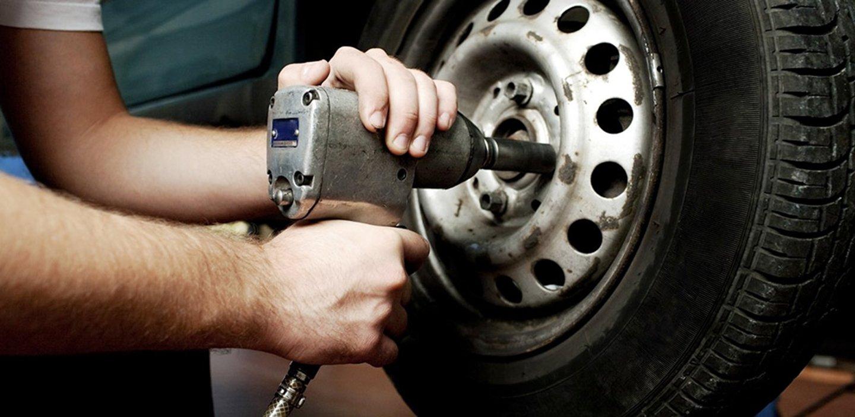 meccanico mentre sostituisce una ruota di un'auto