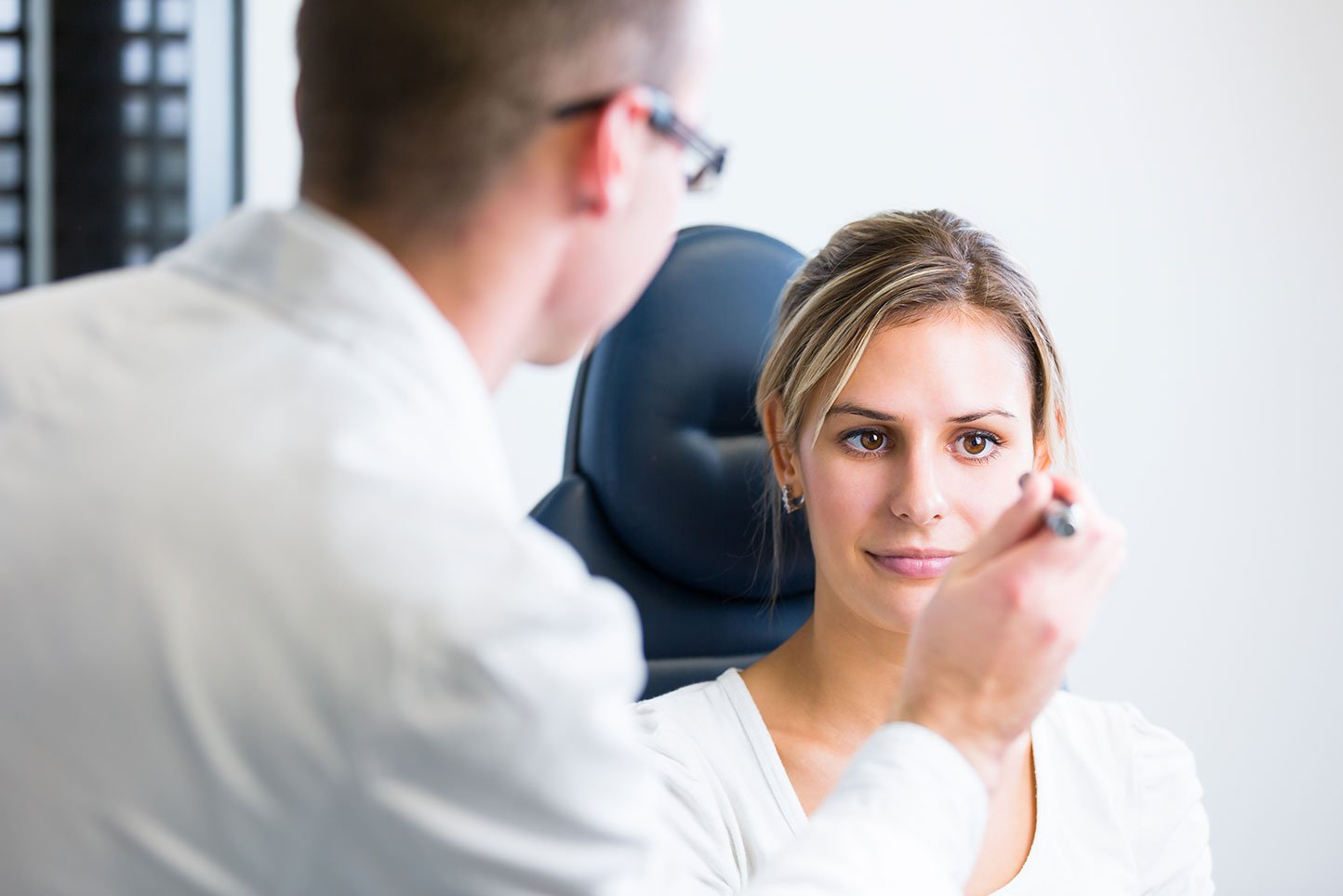 Young woman having her eyes examined by an eye doctor