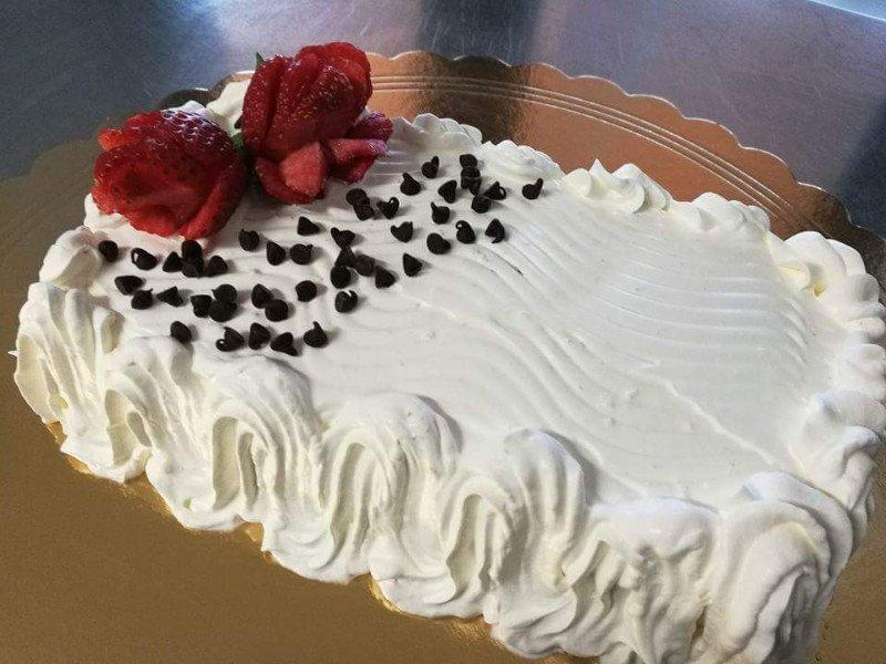 una torta decorato con panna, gocce di cioccolato e delle fragole