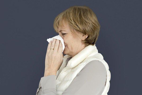 Donna di mezza età si soffia il naso