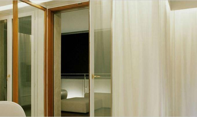 delle porte finestre interne con le tende bianche