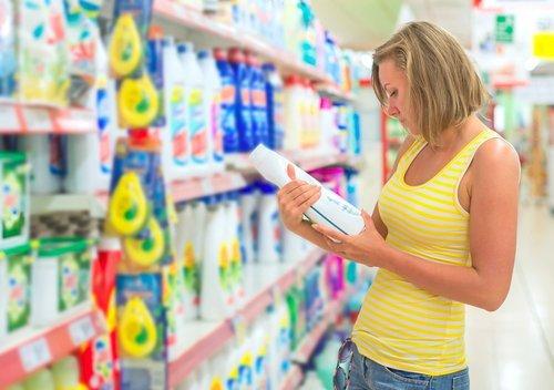 donna che legge l'etichetta di un detersivo