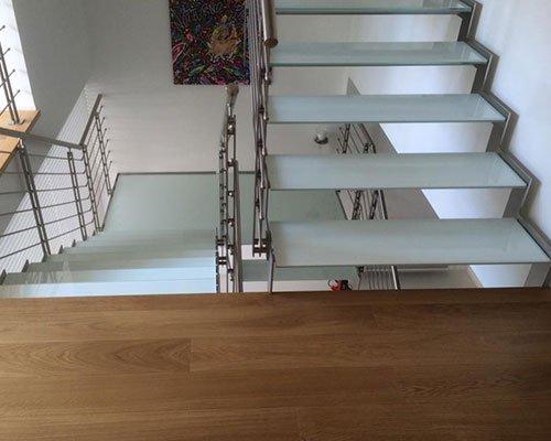 vista di un parquet in legno e di scale in vetro che vanno al piano superiore e inferiore