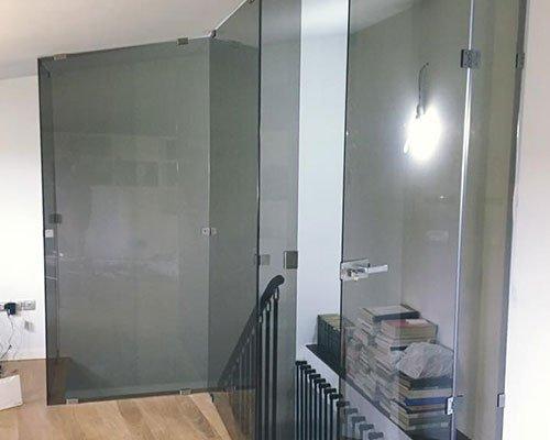 alcune porte in vetro e vista di un corrimano nero di una scala