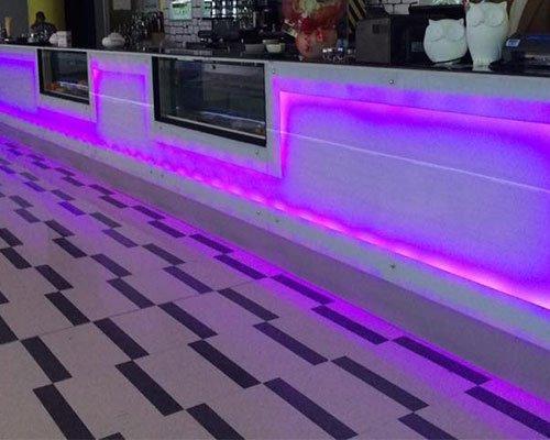 vista di un pavimento bianco e nero in un locale e del bancone in marmo e vetro con delle luci viola e rosa