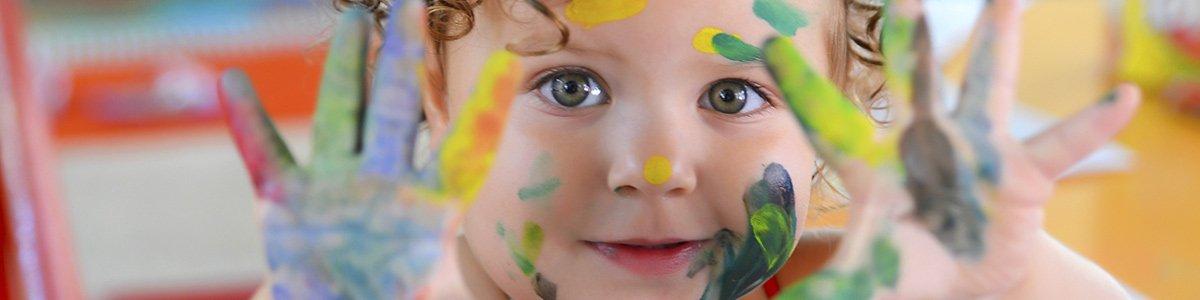 hopskotch kindergarten little girl doing finger painting