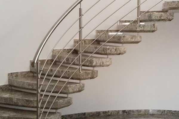scala a curva in granito e scorrimano in acciaio
