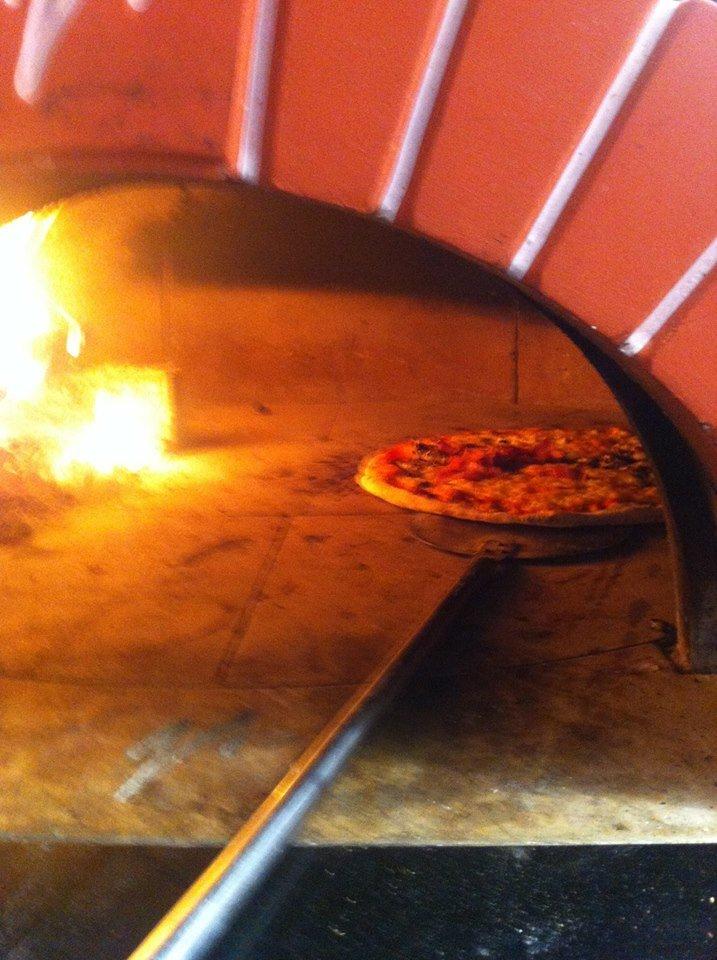 una pizza cotta nel forno a legna