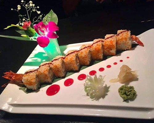 un piatto di sushi con dietro un vaso con dei fiori
