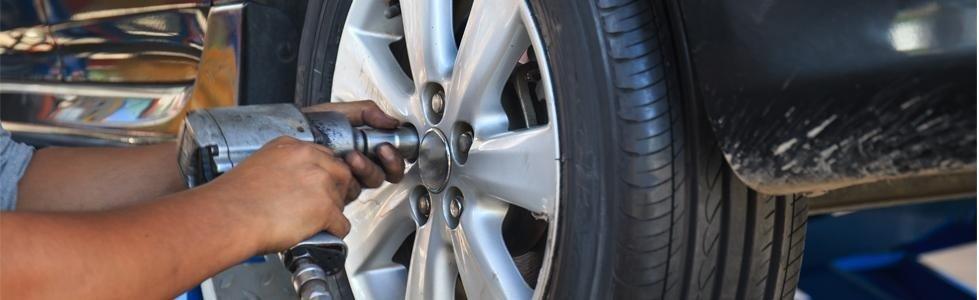 meccanico mentre avvita i bulloni di una ruota
