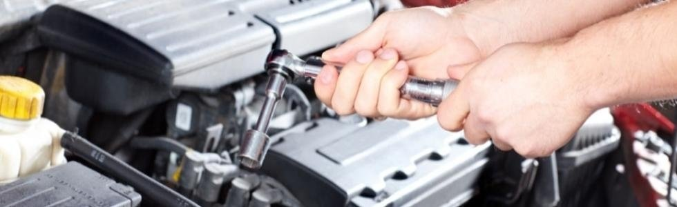 mani che assicurano il fissaggio di alcune componenti meccaniche in un auto