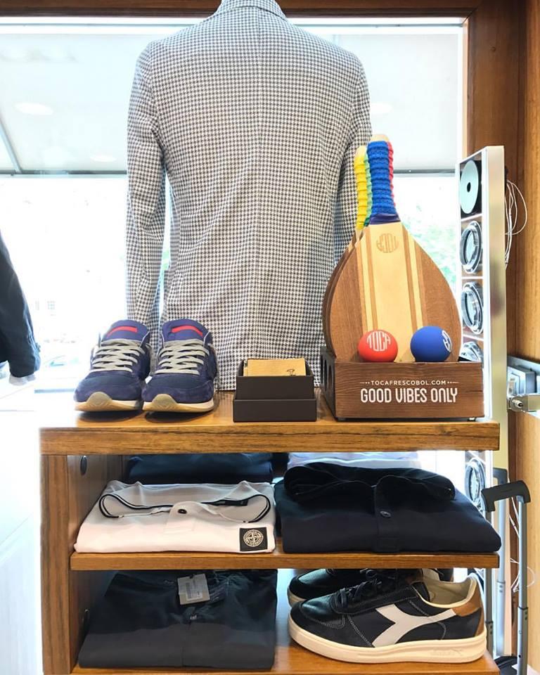 un manichino con una camicia a scacchi e delle mensole con le camicie e delle scarpe sportive